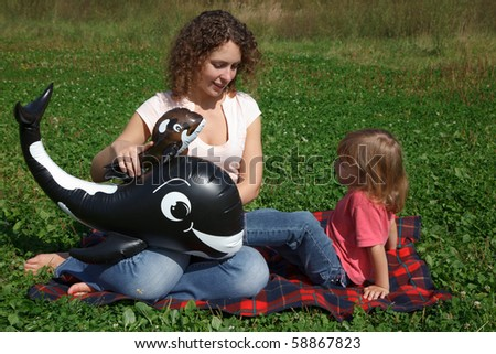 Mom and daughter play on grass on sunny day with inflatable toys.