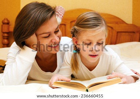 Mom and daughter reading   together a funny book