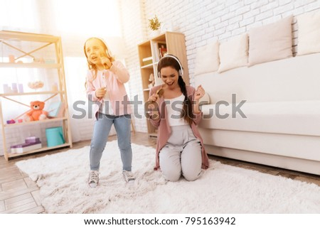 Mom and daughter sing songs at home. They use combs like microphones. They play together. #795163942