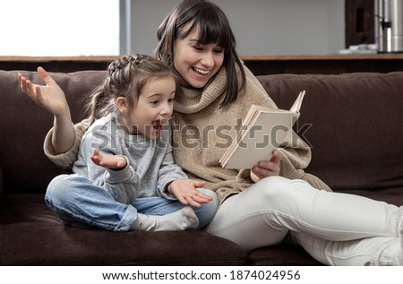 Mom and daughter spend time together reading a book. The concept of children's development and quality time. Foto stock ©