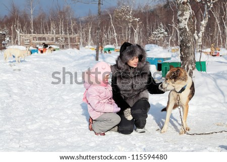 Mom and daughter stroking the dog in the kennel, Siberia, Russia