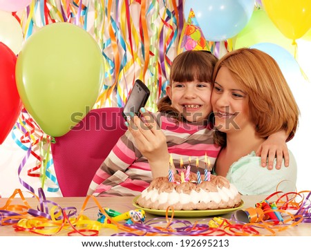 Mom and daughter take pictures at a birthday party