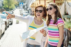 Mom and daughter teenager tourist looking at the map on the street of city