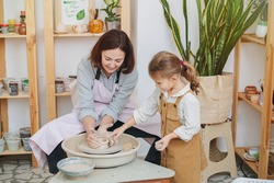 Mom and daughter together, having fun playing with clay make a pot for a potter's wheel in the home studio