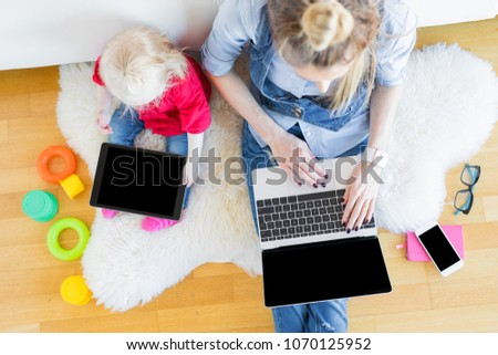Mom and daughter using tech gadgets together #1070125952