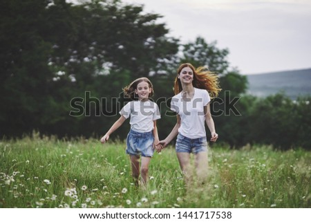 Mom and daughter walking in the field fun childhood childhood countryside leisure movement