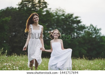 Mom and daughter walking in the field holding hands fun childhood childhood joy flowers