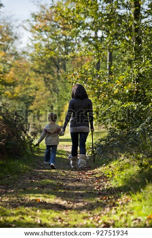 Mom and daughter wander among the trees, learning about trees and animals