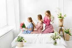 Mom and daughters comb and braid each other's hair. Daily morning care. A bouquet of tulips in the hands of a girl.