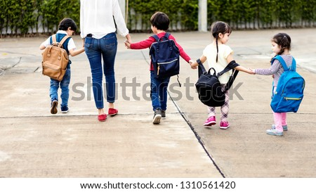 Mom and four kindergarten kids holding hand carry schoolbag walking to school bus.preschool concept.first day of semester #1310561420