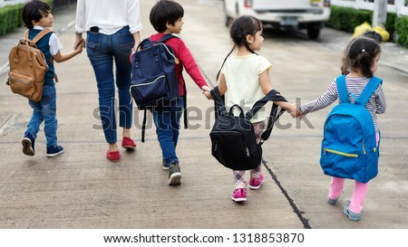 Mom and four kindergarten kids holding hand carry schoolbag walking to school bus.preschool concept.first day of semester #1318853870