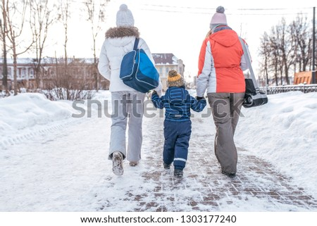 Mom and girlfriend sees boy s son 4-7 years old by the hand walking down the street. Back view. Winter in city on background of snowdrifts. Returning home from event. Two women girlfriends, parents. #1303177240
