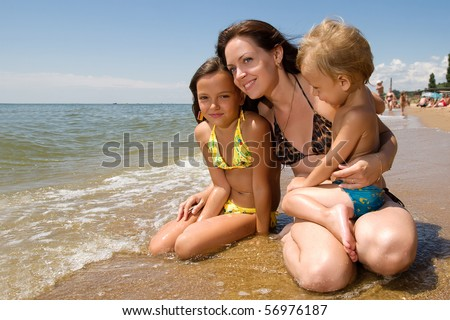 Mom and her children enjoying their summer vacation at the seaside.Young white mother,little daughter and son playing on the beach.Happy young family with friendly smile on face.Good weather day