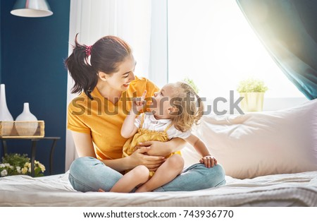 Mom and her daughter child girl are playing, smiling and hugging. Family holiday and togetherness. #743936770