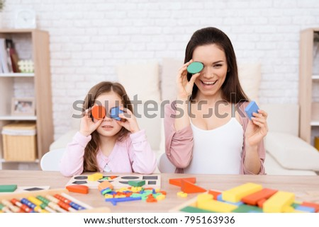 Mom and her little daughter are playing with geometric figures. The figures are made of wood. Woman and girl at home. #795163936
