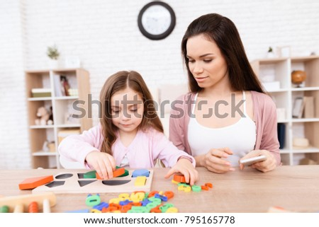 Mom and her little daughter are playing with geometric figures. The figures are made of wood. Woman and girl at home. #795165778