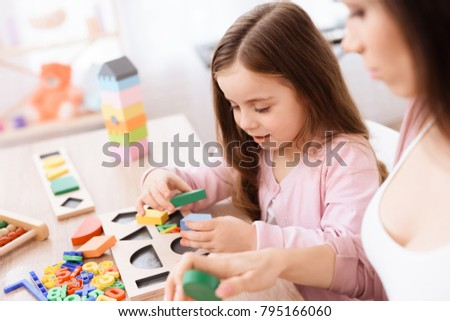 Mom and her little daughter are playing with geometric figures. The figures are made of wood. Woman and girl at home. #795166060