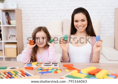 Mom and her little daughter are playing with geometric figures. The figures are made of wood. Woman and girl at home. #795166063