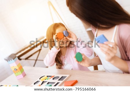 Mom and her little daughter are playing with geometric figures. The figures are made of wood. Woman and girl at home. #795166066