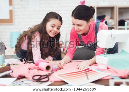 Mom and little daughter together sew clothes. They are in the sewing workshop. They are in a good mood. #1044263689