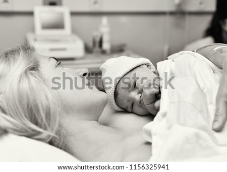 Mom and newborn baby skin to the skin after birth in the hospital