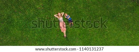 Mom and son are lying on the grass in the park, photos from the drone, quadracopter. BANNER long format Foto stock ©