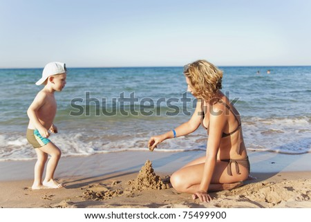 Mom and son building a sand castle on a beach