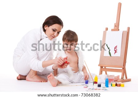Mom and son dressed in white learning to paint near easel