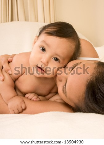 Mom and son lying down on bed and mother embracing the infant baby, who looks at camera with serious facial expression