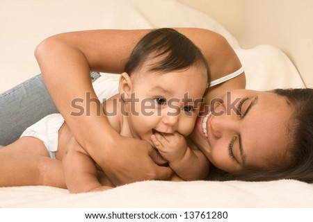 Mom and son lying down on bed and mother embracing the infant baby, who put his hand into mouth