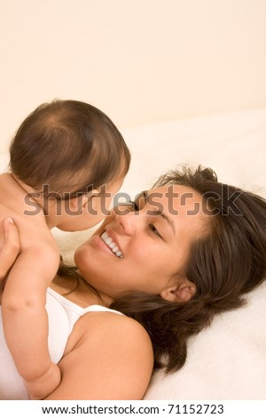 Mom and son on bed and mother embracing the infant baby playing with him