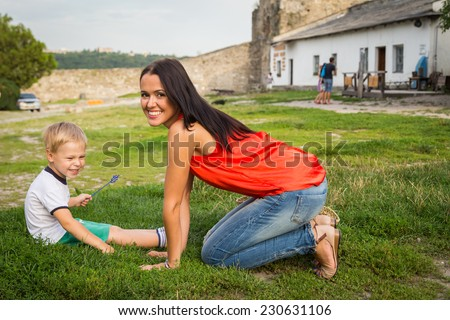 Mom and son outdoors. Mom and son lying on the grass. Mom hugging her son. Holidays, family, nature, children - the concept of a family holiday in the countryside.