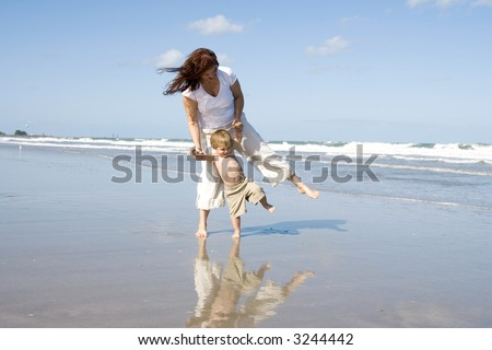 Mom and son playing on a beach, ocean and blue sky in the background