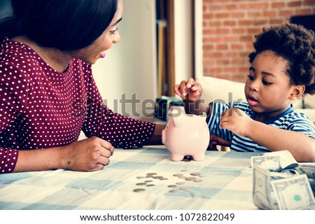Mom and son saving money to piggy bank