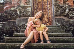 Mom and son travelers in the background of Pura Taman Kemuda Saraswati Temple in Ubud, Bali island, Indonesia BANNER, long format Traveling with children concept