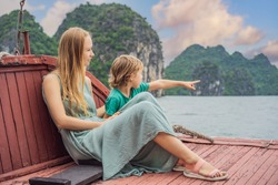 Mom and son travelers is traveling by boat in Halong Bay. Vietnam. Travel to Asia, happiness emotion, summer holiday concept. Traveling with children concept. After COVID 19. Picturesque sea landscape