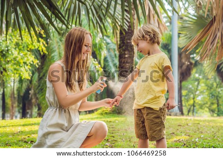 Mom and son use mosquito spray.Spraying insect repellent on skin outdoor