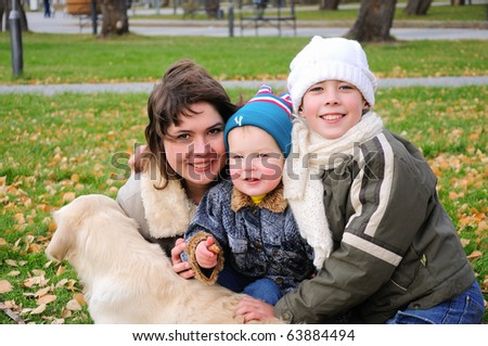 Mom and two sons together having fun in the autumn park playing with the dog