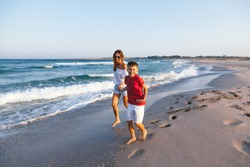 Mom and 8 years old son walking and playing on sunset beach