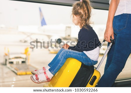 Mom carries your luggage with happy baby at the airport terminal. Flying for holliday, traveling with you luggage safety through Singapore airport. Use businesses class for you comfort #1030592266