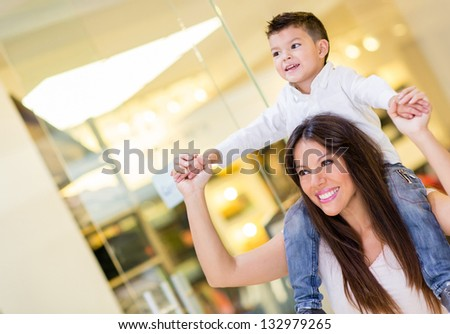Mom carrying her son in her shoulders at the mall