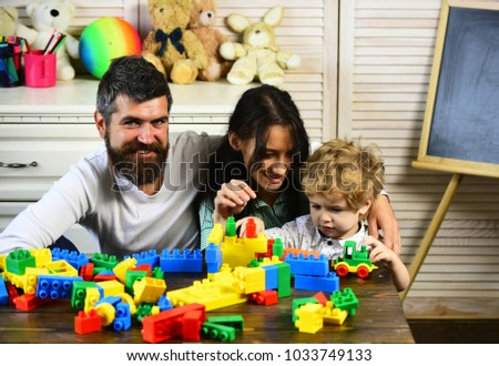 Mom, dad and boy with toys on background build out of plastic blocks. Parents and son with happy faces make brick constructions. Young family spends time in playroom. Love and family games concept #1033749133