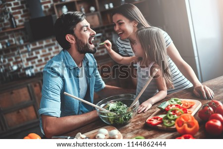 Mom, dad and daughter are cooking on kitchen. Happy family concept. Handsome man, attractive young woman and their cute little daughter are making salad together. Healthy lifestyle.
