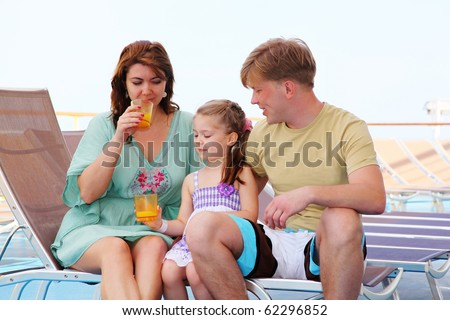 mom dad and daughter rest on deck of yacht and drink tasty juice - stock photo