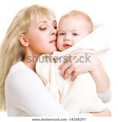 Mom embracing her beautiful baby son covered with towel - stock photo