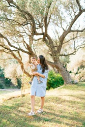 Mom gently holds her little son in her arms against the background of trees in an olive grove