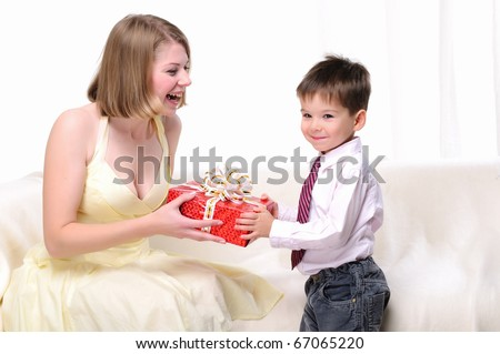 stock photo mom giving a gift to his son sitting on a white sofa 67065220
