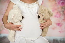 Mom hands holding two bear. Pregnant woman's belly. Twins