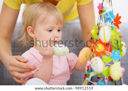 Mom helping baby made Easter decoration - stock photo