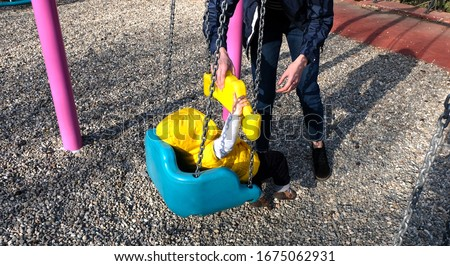 Mom helping her baby boy getting off the swing Stok fotoğraf ©